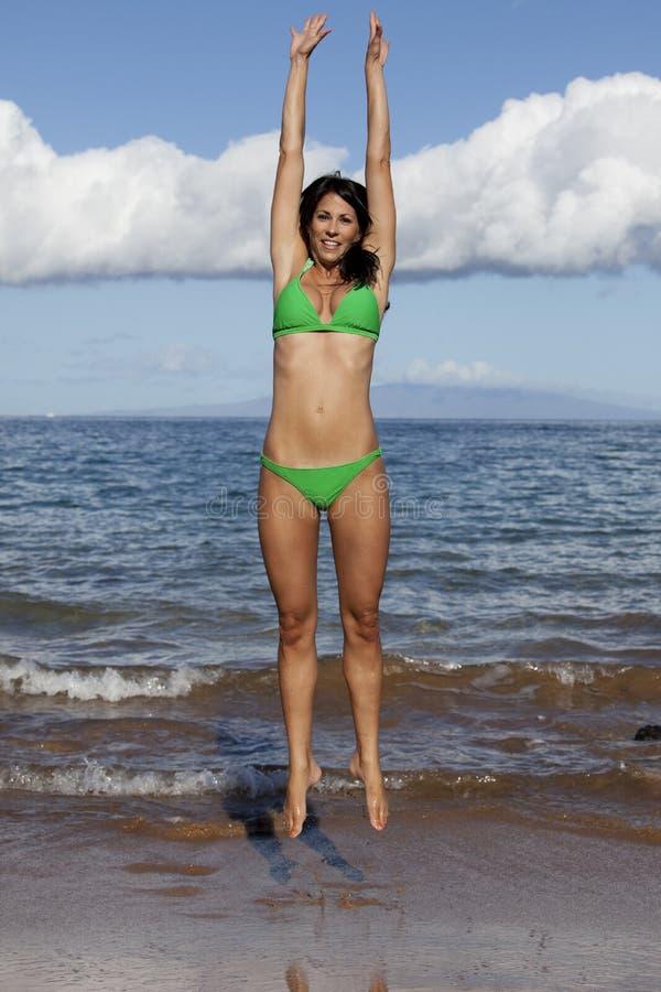 Het springen op het strand stock fotografie