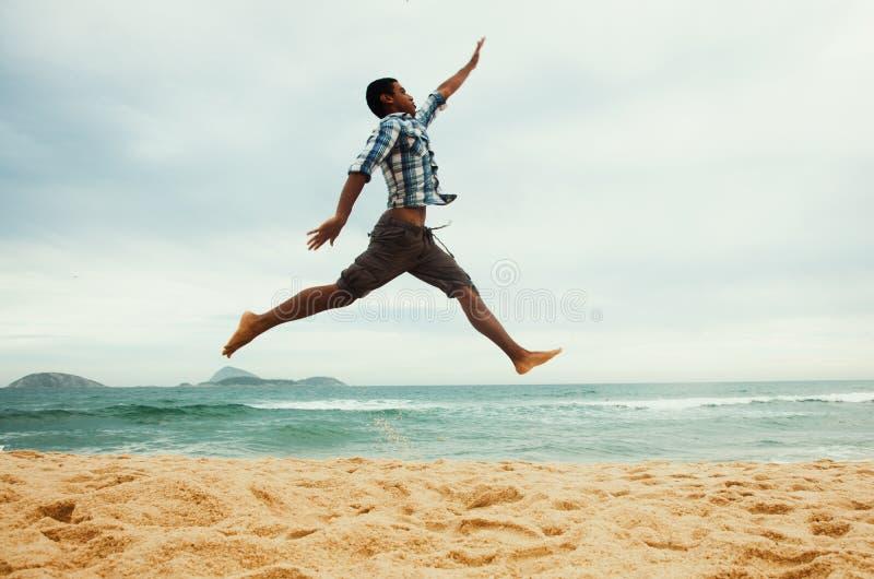 Het springen van Latijnse kerel bij strand royalty-vrije stock foto
