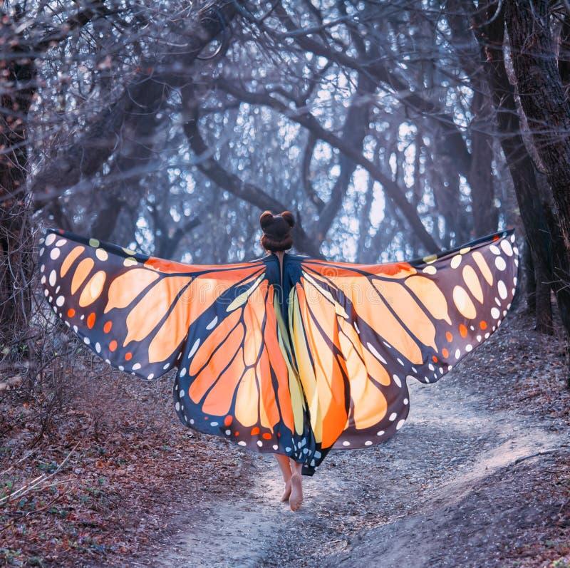 Het sprookje over vlinder, geheimzinnig verhaal van meisje met rood haar en grote lichtoranje vleugels, dame loopt blootvoets  royalty-vrije stock afbeeldingen