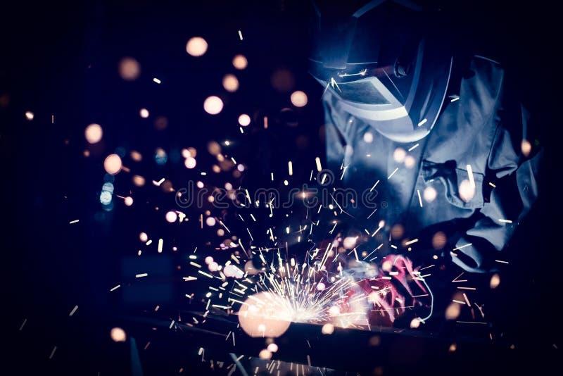 Het staal van het arbeiderslassen met vonken die de lasser van mig met behulp van mag stock foto's