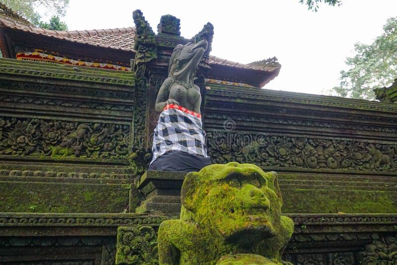 Het standbeeld in de Hindoese Tempel in Ubud-Aapbos dat door mos, het Eiland van Bali, Indonesi? wordt behandeld stock foto