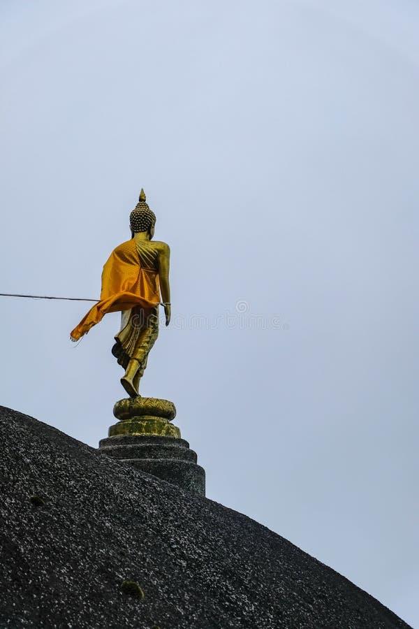 Het standbeeld die van Boedha zich op de berg met gele robe bevinden stock foto