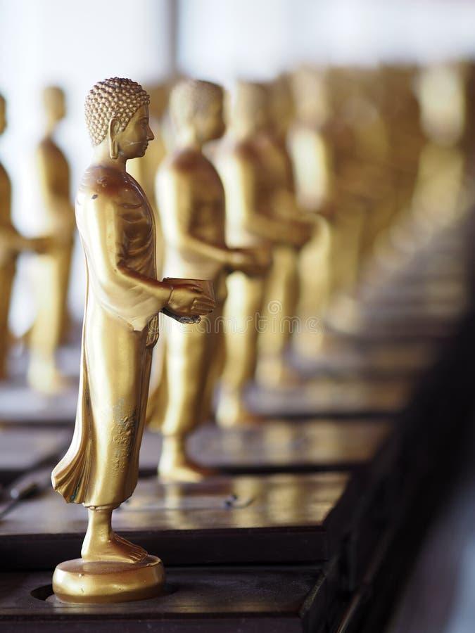 Het standbeeld die van messingsboedha houdend Aalmoes werpt plaatsen in de Kapel, Paviljoen bij een tempel bevinden zich royalty-vrije stock foto