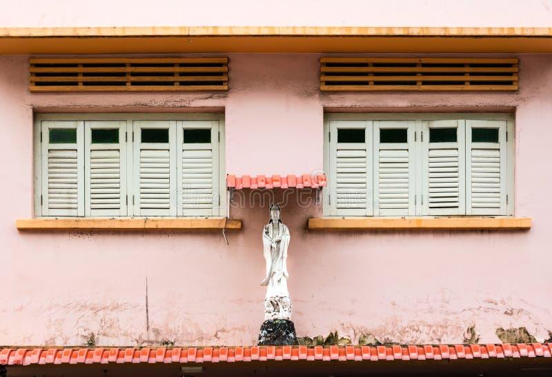 Het standbeeld van Boedha in de voorzijde van de oude het venstervoorgevel van het winkelhuis royalty-vrije stock foto's