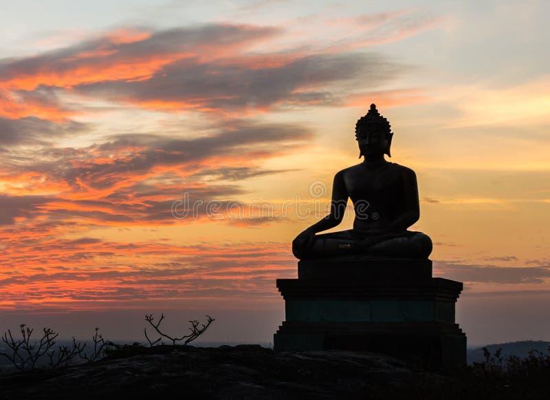 Het standbeeld van Boedha op de achtergrond van de zonsonderganghemel stock afbeelding