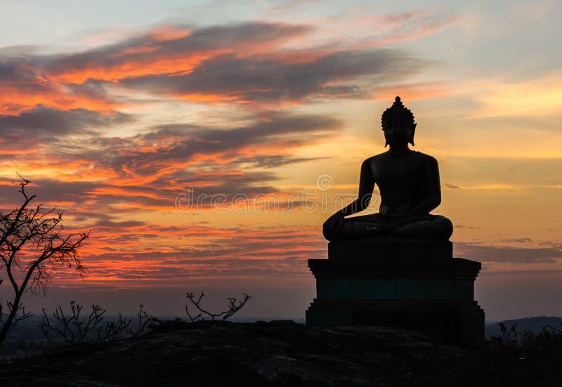 Het standbeeld van Boedha op de achtergrond van de zonsonderganghemel in Thailand stock afbeeldingen