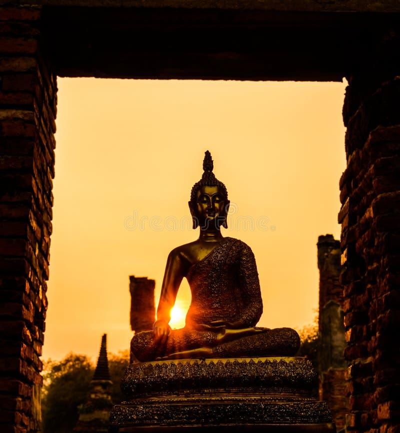 Het standbeeld van Boedha op zonsondergang in Ayutthaya stock afbeelding