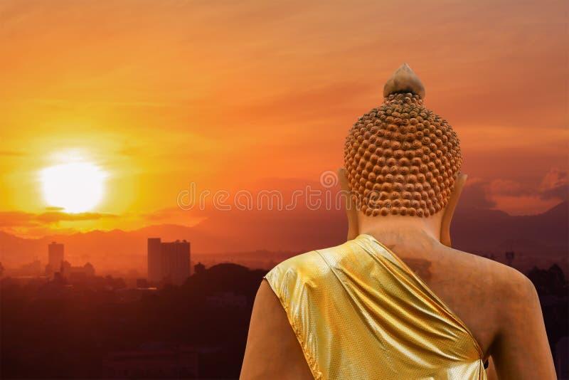 Het standbeeld van Boedha op zonsonderganghemel en mooie de achtergrond van het stadsonduidelijke beeld stock afbeelding