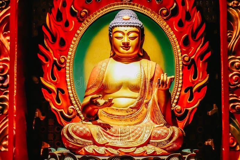 Het standbeeld van de zitting van Boedha in meditatie en wachten voor Nirvana met dient ritueel gebaar in Binnen de Tempel van he stock foto