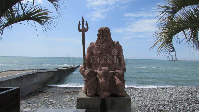 Het standbeeld van Poseidon op de kustdijk in Sotchi, zuidelijk Rusland De Zwarte Zee, palmen, kiezelsteenstrand stock afbeelding