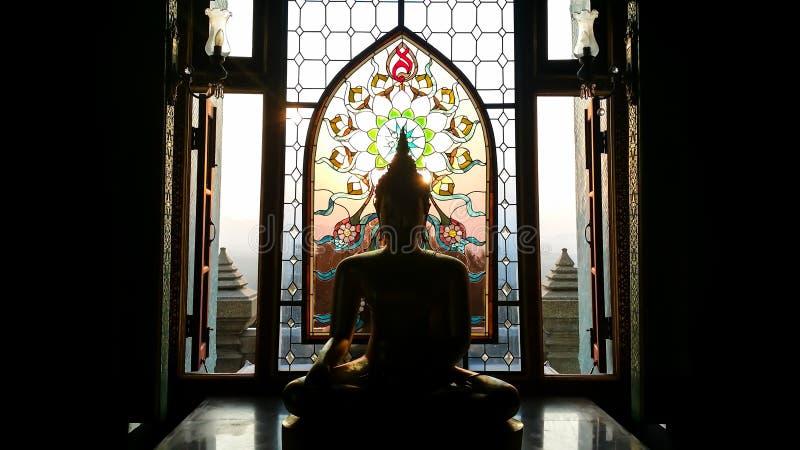 Het standbeeld van silhouetboedha heeft bloem en zonpatroon bevlekte gla stock foto