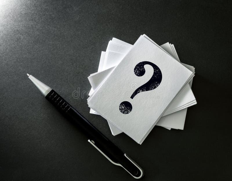 Het stapelen van een wit adreskaartje met geschreven vraagteken sym stock afbeelding