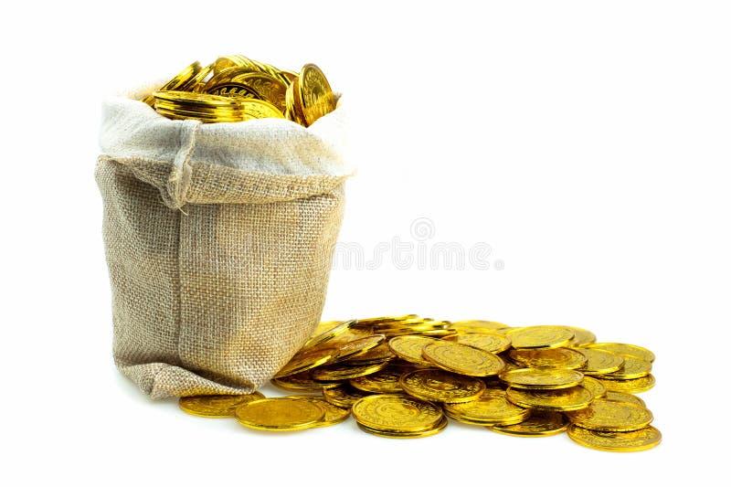 Het stapelen van gouden muntstuk in schatzak op witte achtergrond royalty-vrije stock fotografie