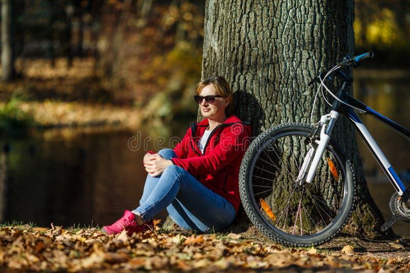 Het stedelijke biking - vrouwen berijdende fiets in stadspark stock afbeelding