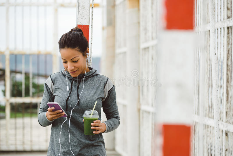 Het stedelijke geschiktheidsvrouw texting op haar smarphone royalty-vrije stock afbeeldingen