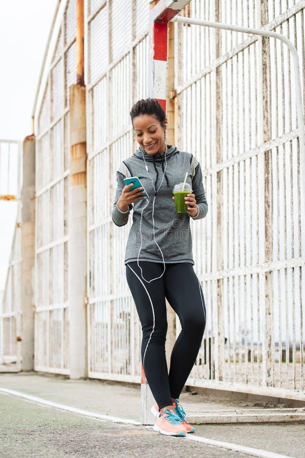 Het stedelijke geschiktheidsvrouw texting op haar smarphone stock afbeelding