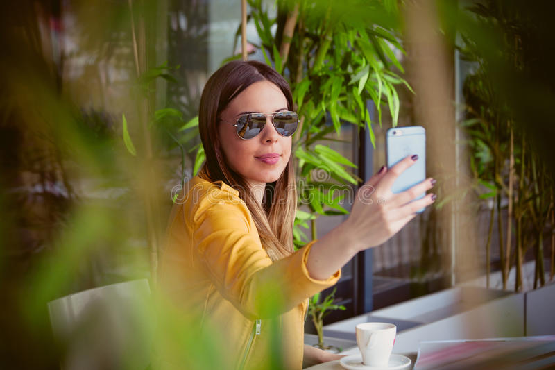Het stedelijke meisje zit in koffie het openlucht nemen selfie royalty-vrije stock afbeelding