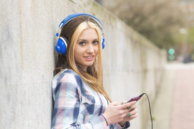 Het stedelijke portret vrolijke mooie meisje luistert muziek met headpho stock foto