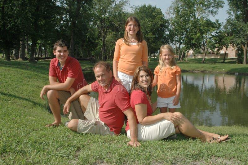 Het stellen van de familie door vijver stock afbeeldingen