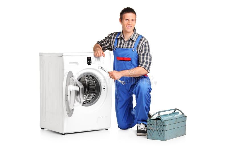 Het stellen van de hersteller naast een wasmachine royalty-vrije stock afbeeldingen