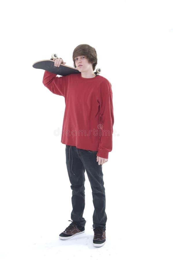 Het stellen van de jongen met skateboard op schouder stock afbeeldingen
