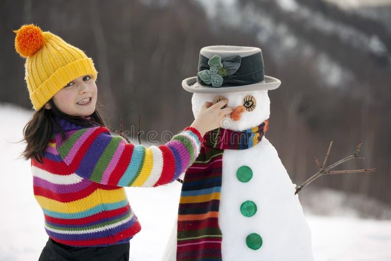 Het stellen van het meisje met haar sneeuwman stock foto's