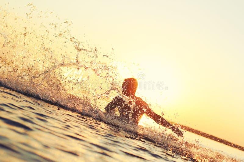Het sterke atleet bespatten in het water bij zonsondergang royalty-vrije stock foto