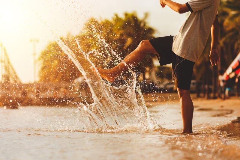 Het sterke jongen schoppen op oppervlakte die van zeewater met zijn been plons op strand maken royalty-vrije stock foto's