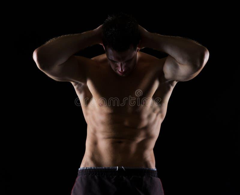 Het sterke mannelijke atleet stellen op zwarte royalty-vrije stock foto