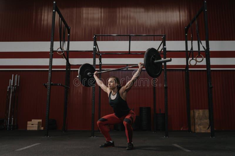 Het sterke vrouw lucht opheffen barbell, doend crossfit oefeningen royalty-vrije stock afbeelding