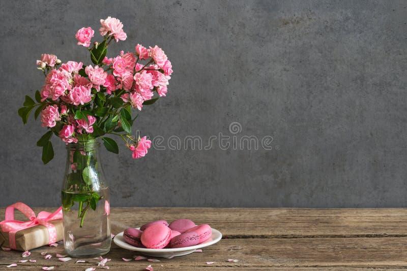 Het stilleven met een mooi boeket van roze rozen bloeit, macarons en giftdoos vakantie of huwelijksachtergrond royalty-vrije stock foto's