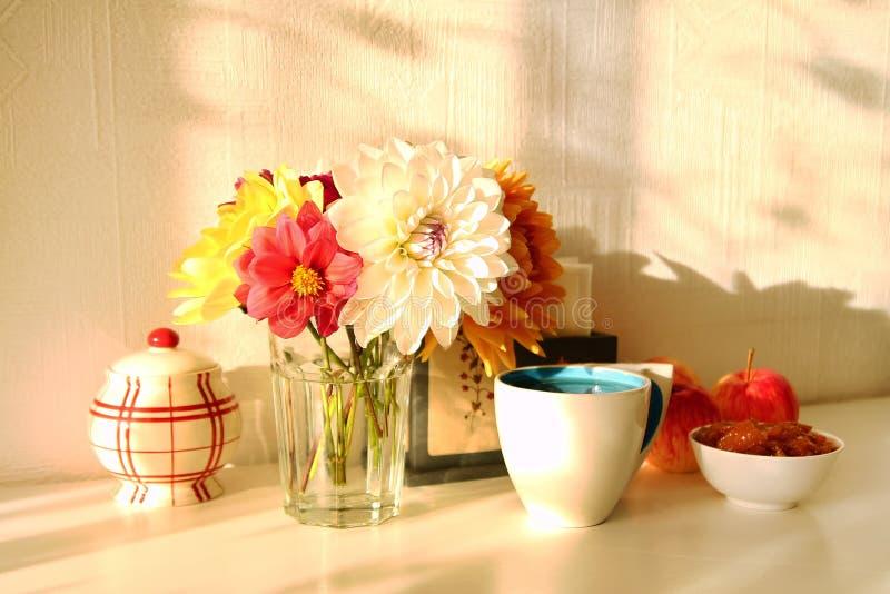 Het stilleven met glasvaas met kleurrijke bloemen van pioenen, de kop thee, de appeljam, de appelen en de suiker werpen op de wit stock foto