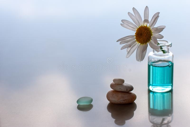 Het stilleven met kamille als zon plakte in een fles met aromatische olie en stenen in de vorm van een piramide naast en een glas stock foto's