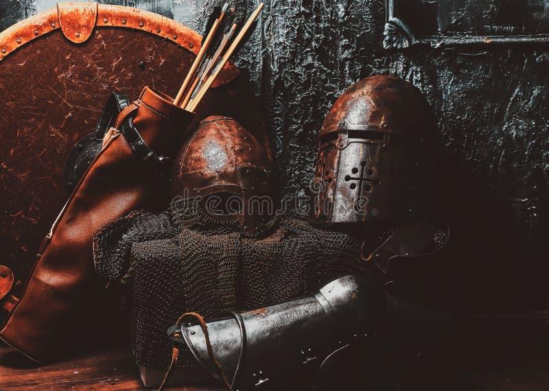 Het stilleven met oud schild, twee roestte helmen, quiver van pijlen stock afbeelding