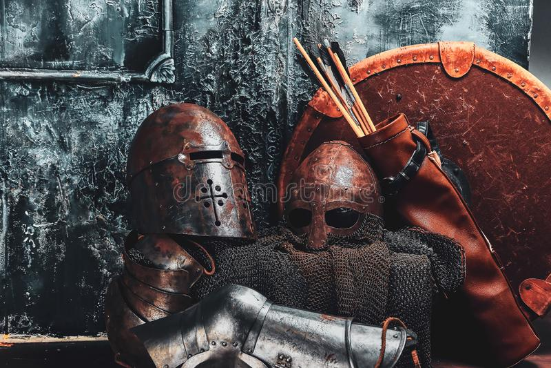 Het stilleven met oud schild, twee roestte helmen, quiver van pijlen stock foto's