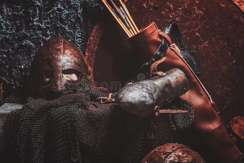 Het stilleven met oud schild, twee roestte helmen, quiver van pijlen royalty-vrije stock afbeelding