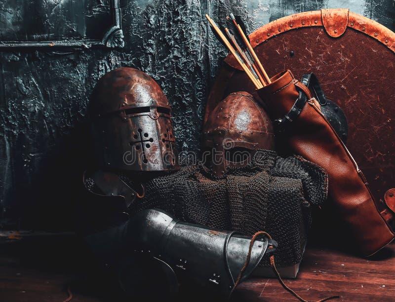 Het stilleven met oud schild, twee roestte helmen, quiver van pijlen stock foto