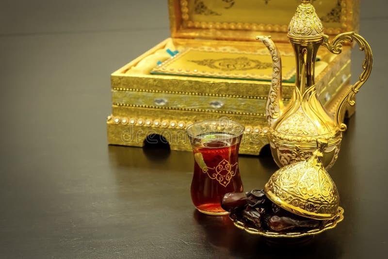 Het stilleven met traditionele luxe gouden Arabische koffie plaatste met dallah, kop en data De achtergrond van het Quranboek Ram stock foto's