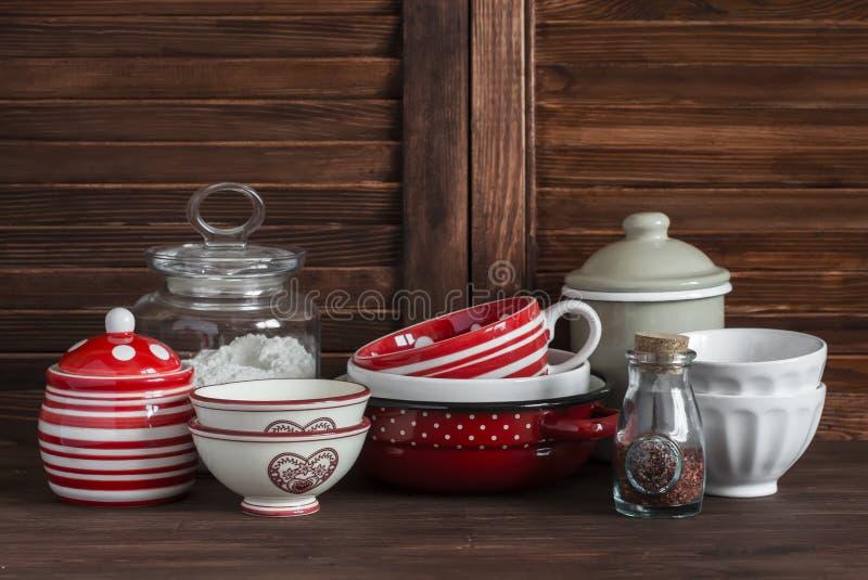 Het stilleven van de keuken Uitstekend aardewerk - de kruik bloem, ceramische kommen, pan, emailleerde kruik, juskom Op een donke stock afbeeldingen