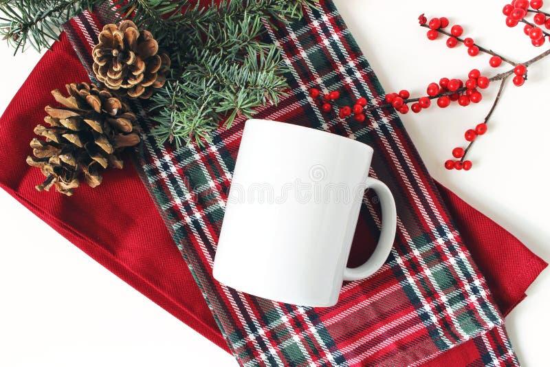 Het stilleven van de winter Lege koffiemok, sparrentak, hulstbessen en denneappels Geruite geruit Schots wollen stofplaid Kerstmi royalty-vrije stock foto