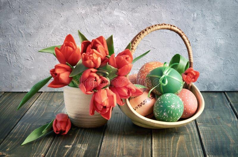 Het stilleven van Pasen Rode tulpen en een mand van het rode en groene Oosten