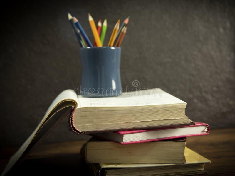 Het stillevenboek in bibliotheek met potloden kleurt in potloodgeval op donker achtergrondonderwijsconcept terug naar school royalty-vrije stock afbeelding