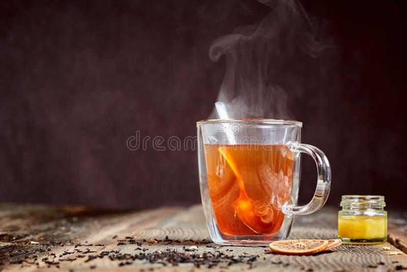 Het stomen van hete thee en honing op een houten lijst stock afbeelding