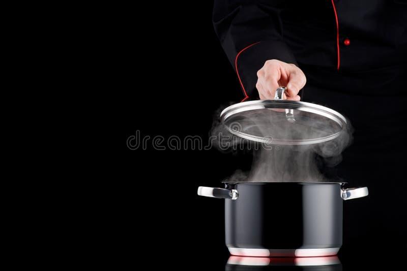 Het stomen van pot op inductiekooktoestel, moderne chef-kok in professio stock fotografie