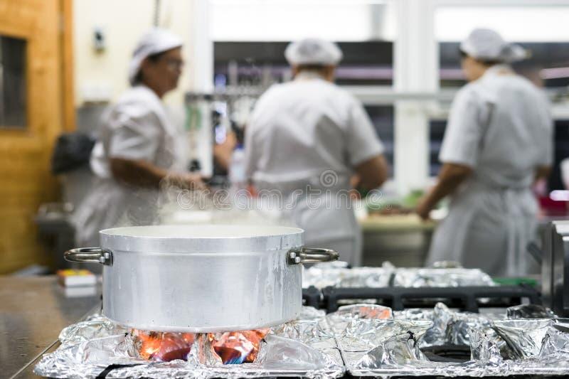 Het stomen van zilveren pot met drie keukenarbeiders in restaurant stock foto's