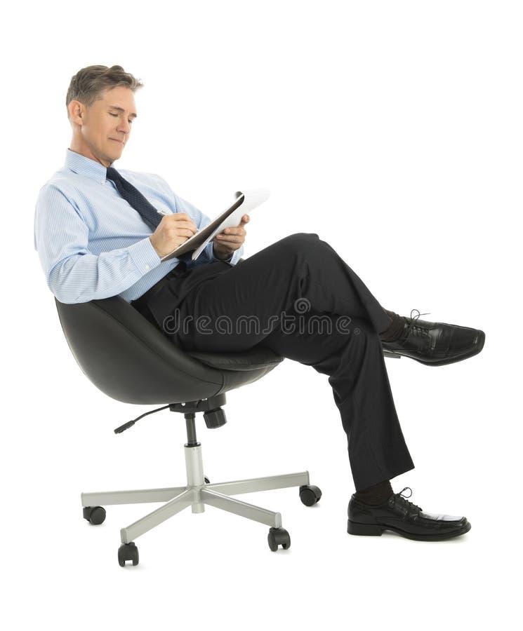 Het Stootkussen van zakenmanwriting in note terwijl het Zitten op Bureaustoel royalty-vrije stock afbeeldingen
