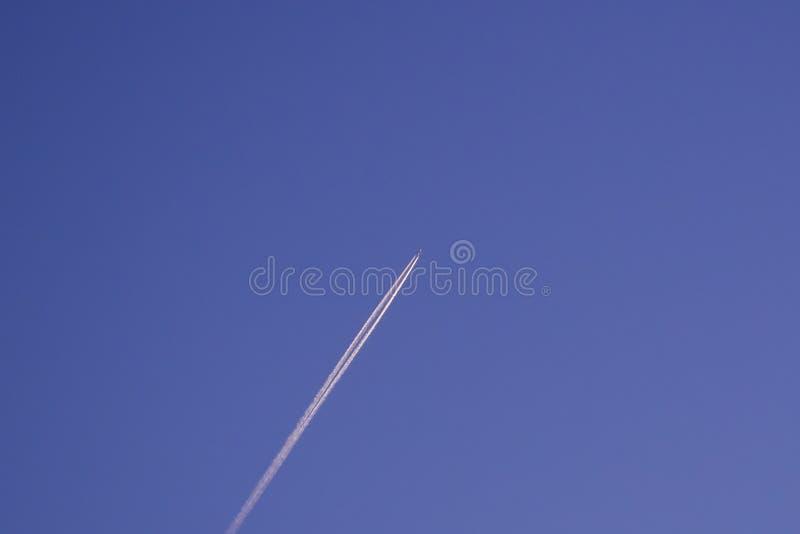 Het straallijnvliegtuigvliegtuig die bij hoge hoogte vliegen verlaat dampsleep/contrail tegen donkerblauwe hemel stock foto's