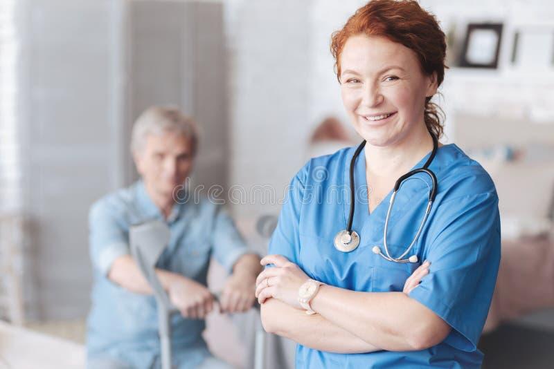 Het stralende vrouwelijke verzorger stellen met haar gekruiste wapens stock afbeelding