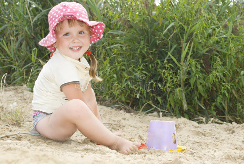 Het strand bij het meer in het zand een klein meisje in een hoed playin stock fotografie
