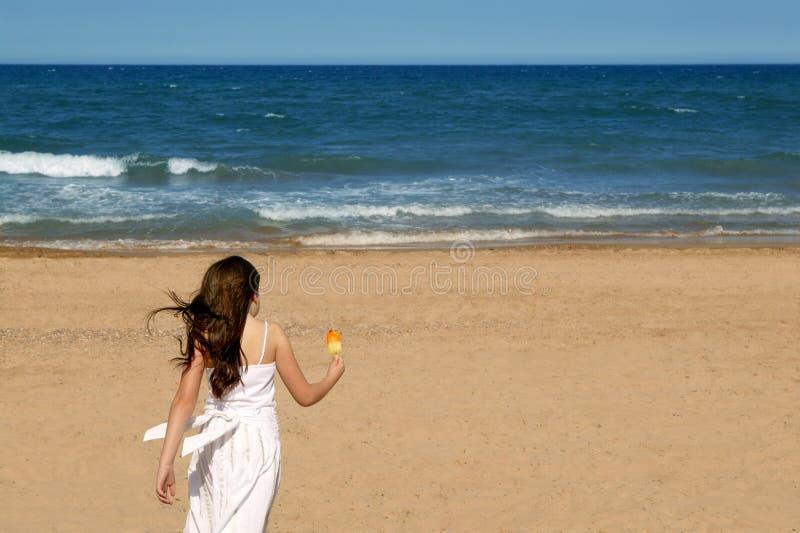 Het strand dat van de het meisjeszomer van de tiener met roomijs loopt stock foto